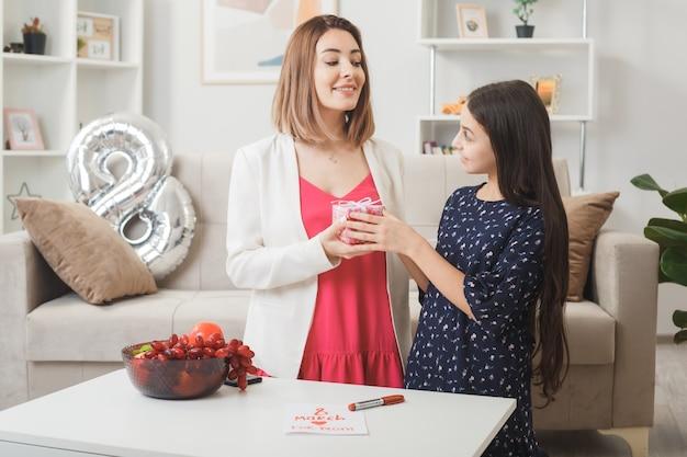 Sorrindo, olhando uma para a outra, a filha dá um presente para a mãe no feliz dia da mulher na sala de estar