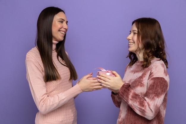 Sorrindo, olhando uma para a outra, duas garotas segurando presentes