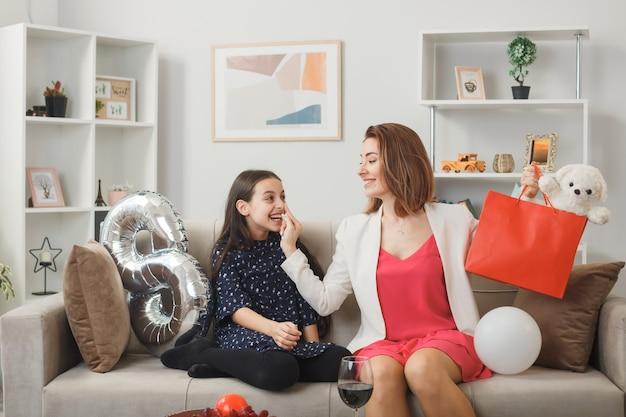 Sorrindo, olhando uma para a outra, garotinha e mãe com ursinho de pelúcia no feliz dia da mulher, sentadas no sofá da sala