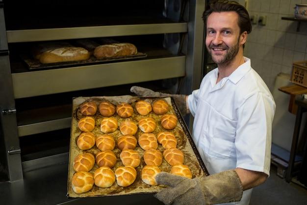 Sorrindo padeiro carregando uma bandeja de bolos cozidos