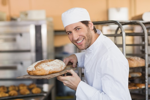 Sorrindo, padeiro, cheirando, pão fresco