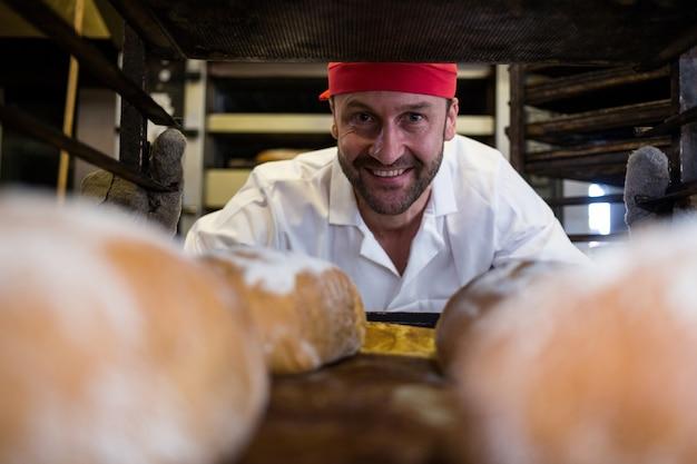 Sorrindo padeiro mantendo a bandeja de pães assados na prateleira