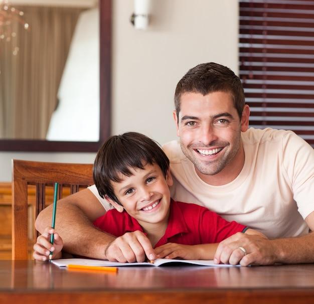 Sorrindo, pai, ajudando, seu, filho, dever casa
