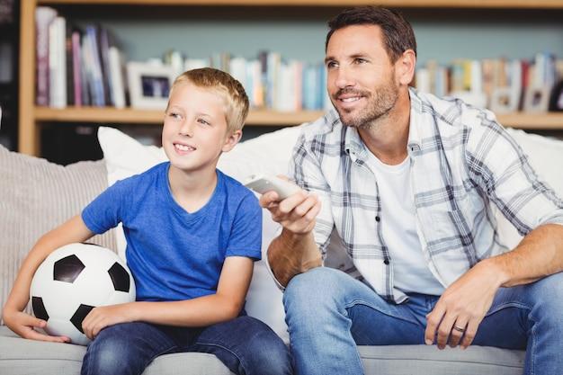 Sorrindo, pai e filho assistindo jogo de futebol