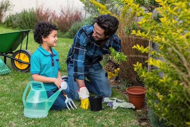 Sorrindo pai e filho jardinando