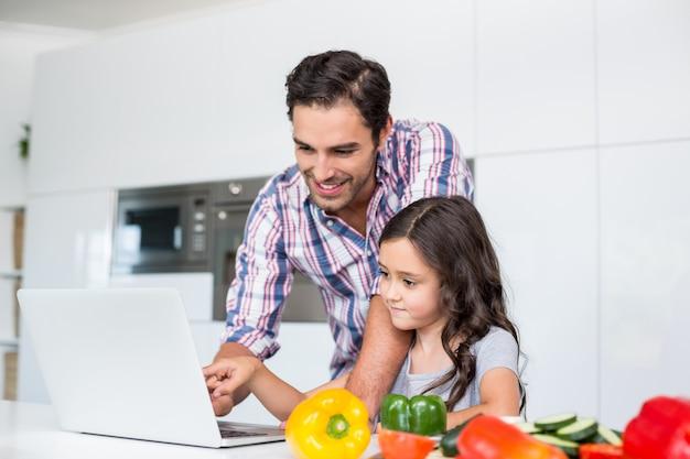 Sorrindo, pai filha, usando computador portátil