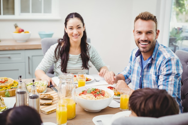 Sorrindo pais com filhos sentados na mesa de jantar