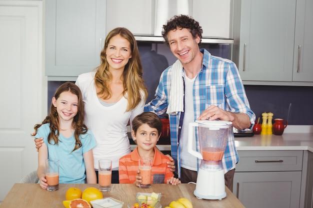 Sorrindo, pais e filhos com suco de frutas