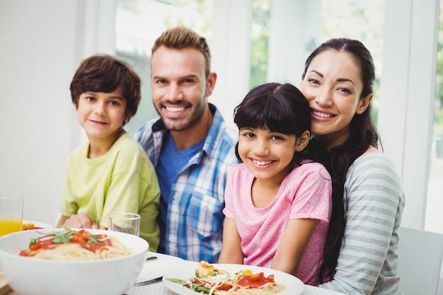 Sorrindo, pais e filhos na mesa de jantar
