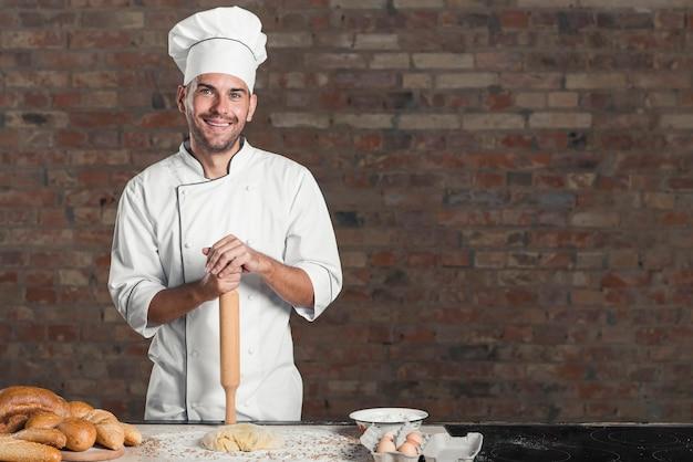 Sorrindo pão assado com massa e ingredientes na bancada da cozinha
