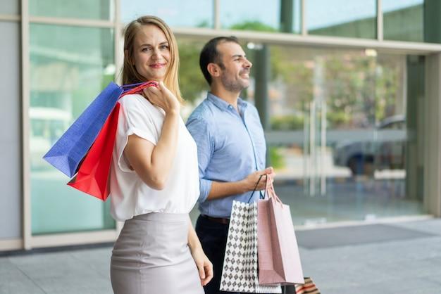 Sorrindo, par adulto, shopping, segurando, sacolas papel, e, andar, ligado, rua cidade