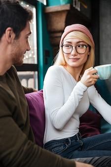 Sorrindo, par amoroso, sentando café, e, bebendo café