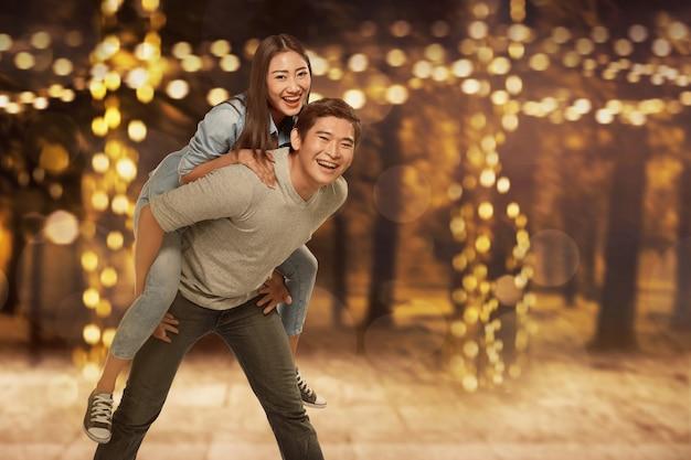 Sorrindo, par asiático, tendo divertimento