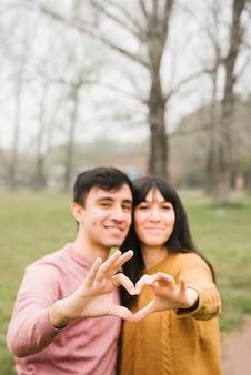 Sorrindo, par jovem, abraçando, mostrando, gesto coração