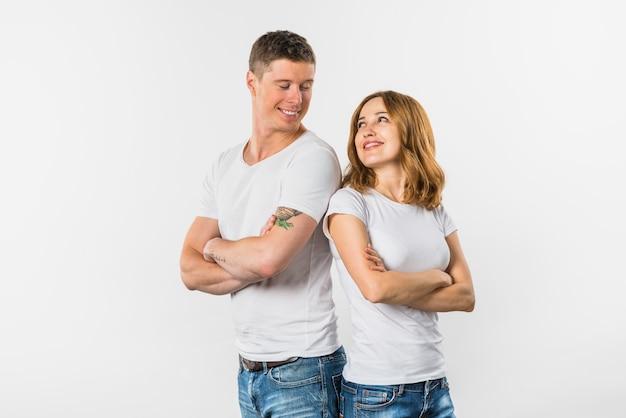 Sorrindo, par jovem, ficar, costas, para, costas, olhando um ao outro, contra, fundo branco