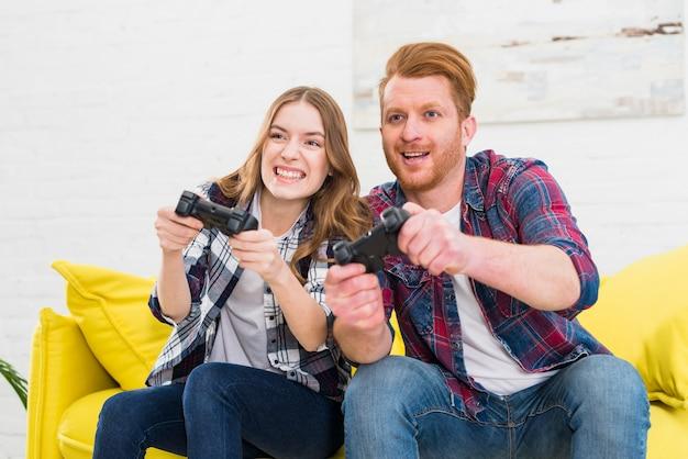 Sorrindo, par jovem, jogando jogos computador, casa