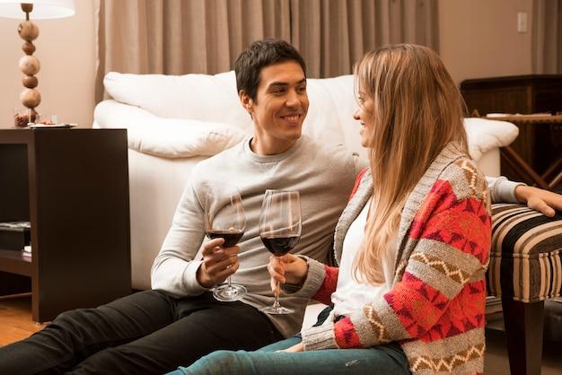 Sorrindo, par jovem, segurando, copos de vinho, em, a, sala de estar