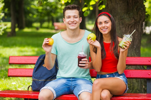 Sorrindo, par jovem, segurando, maçãs, e, smoothies