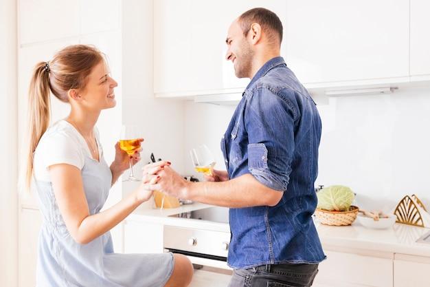 Sorrindo, par jovem, segurar, um, outro, mão, segurando, wineglasses, em, mão, olhando um ao outro
