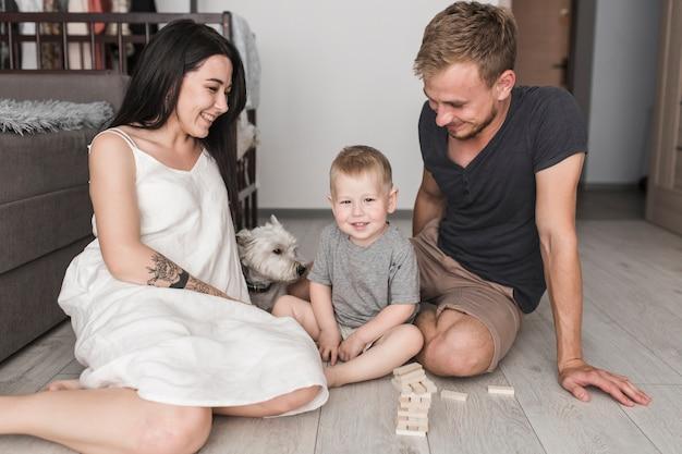 Sorrindo, par jovem, tocando, com, seu, filho, e, cão, casa