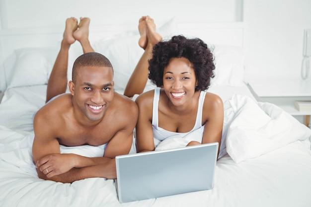 Sorrindo, par, usando computador portátil, cama, casa