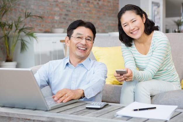 Sorrindo, par, usando computador portátil, e, smartphone, em, a, sala de estar