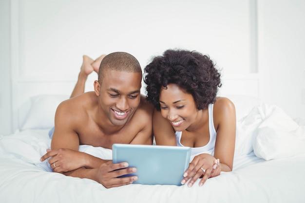 Sorrindo, par, usando, tabuleta, cama, casa
