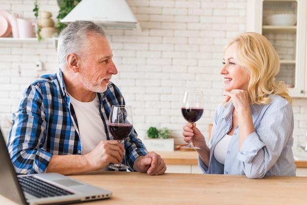 Sorrindo, par velho, copo segurando, de, vinho tinto, em, mão, olhando um ao outro, com, laptop, ligado, tabela