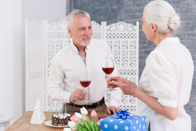 Sorrindo, par velho, desfrutando, aniversário, partido, segurando, vinho tinto, óculos, em, mão