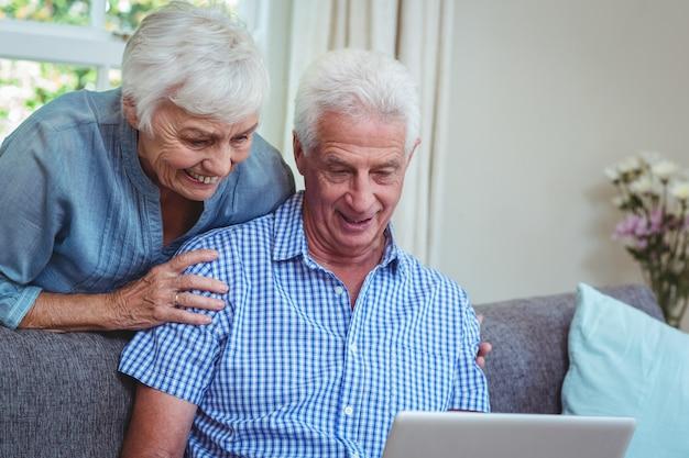 Sorrindo, par velho, discutir, enquanto, usando computador portátil
