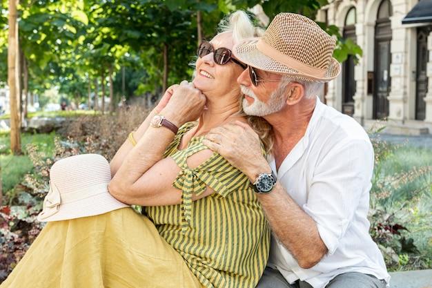 Sorrindo, par velho, sentando um banco
