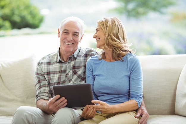 Sorrindo, par velho, sentar sofá, com, tablete digital, em, sala de estar