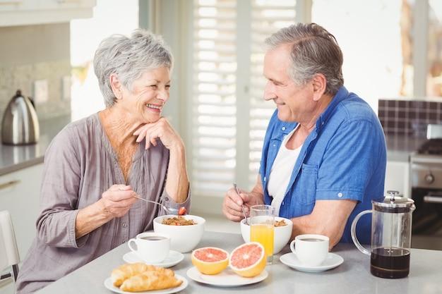 Sorrindo, par velho, tomando café da manhã