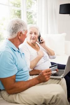 Sorrindo, par velho, usando computador portátil, e, smartphone, casa
