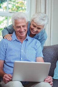 Sorrindo, par velho, usando computador portátil