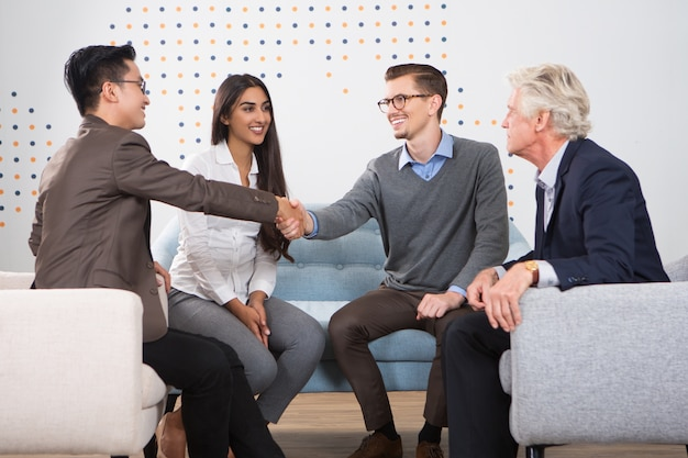 Sorrindo parceiros de negócios apertando as mãos no salão