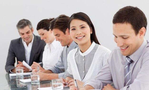 Sorrindo parceiros de negócios tomando notas em uma reunião