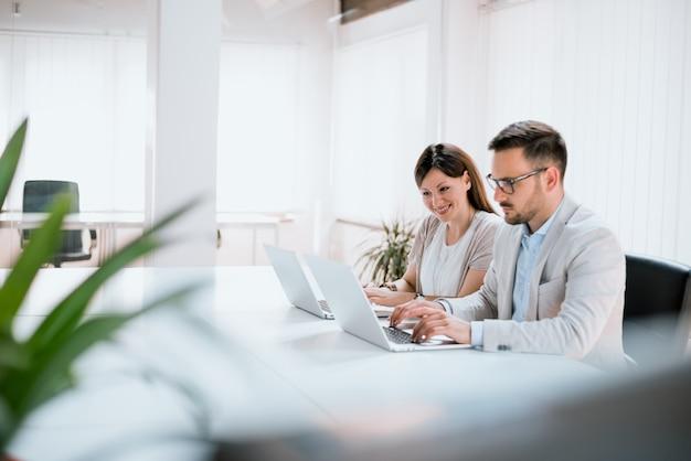 Sorrindo parceiros trabalhando na mesa usando o laptop no escritório