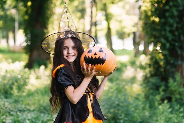 Sorrindo, pequeno, bruxa, segurando, abóbora