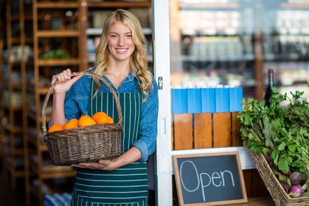 Sorrindo pessoal feminino segurando cesta de frutas no supermercado