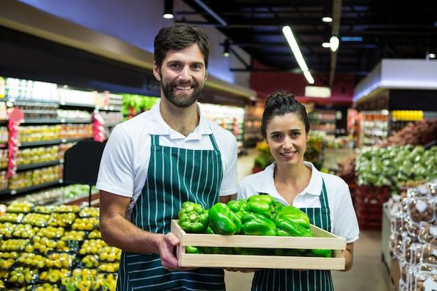 Sorrindo pessoal segurando uma caixa de pimentão verde no supermercado