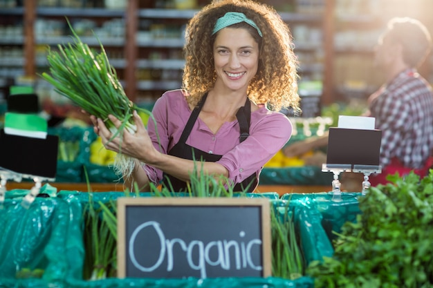 Sorrindo pessoal segurando vegetais na seção orgânica