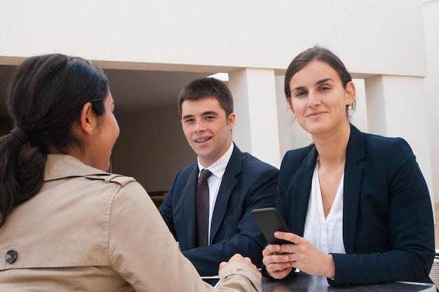 Sorrindo, pessoas negócio, e, cliente, sentando escrivaninha