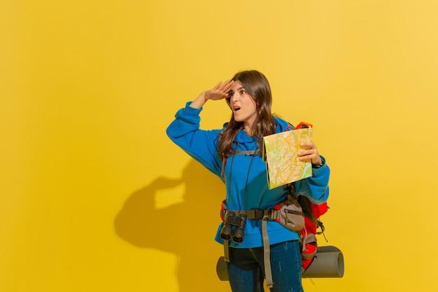 Sorrindo, procurando um jeito. retrato de uma garota alegre jovem turista caucasiano com bolsa e binóculos isolados no fundo amarelo do estúdio. preparando-se para viajar. resort, emoções humanas, férias.