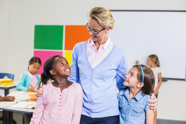 Sorrindo, professor e crianças em pé junto com o braço