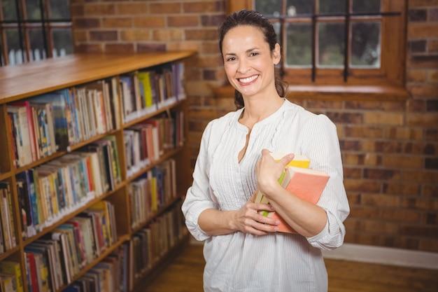 Sorrindo, professor, segurando, livros, em, dela, mãos