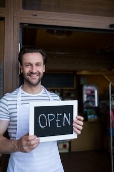 Sorrindo proprietário que prende um sinal aberto na entrada da loja da padaria