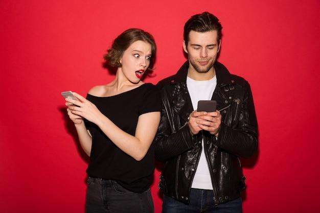 Sorrindo punk masculino usando smartphone enquanto a mulher olha para ele