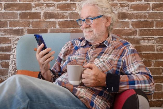 Sorrindo relaxado homem sênior em casa sentado na poltrona usando o smartphone. parede de tijolos no fundo