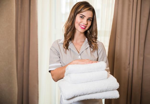 Sorrindo, retrato, de, jovem, chambermaid, segurando, limpo dobrado, empilhado, de, toalha macia, em, mão